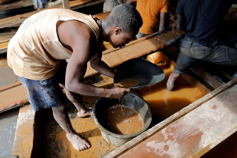 FILE PHOTO: An artisanal miner pans for gold in alluvial sediment over a plastic bucket at the unlicensed mining site of Nsuaem Top in Ghana