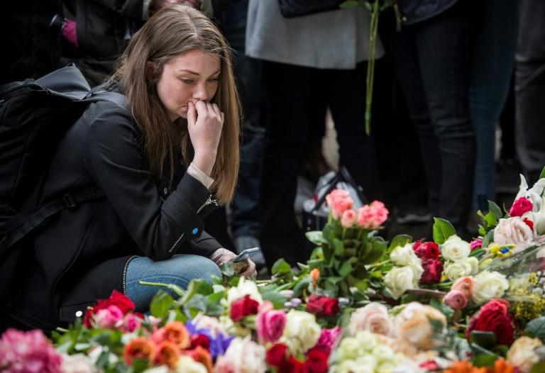 A woman reacts during a minute of silence to commemorate the victims of Friday's terror attack at a makeshift memorial near the site where a truck drove into Ahlens department store in Stockholm, Sweden, on April 10, 2017