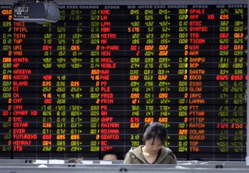 A Thai investor stands infront of an electronic shares price display at the stock exchange in Bangkok