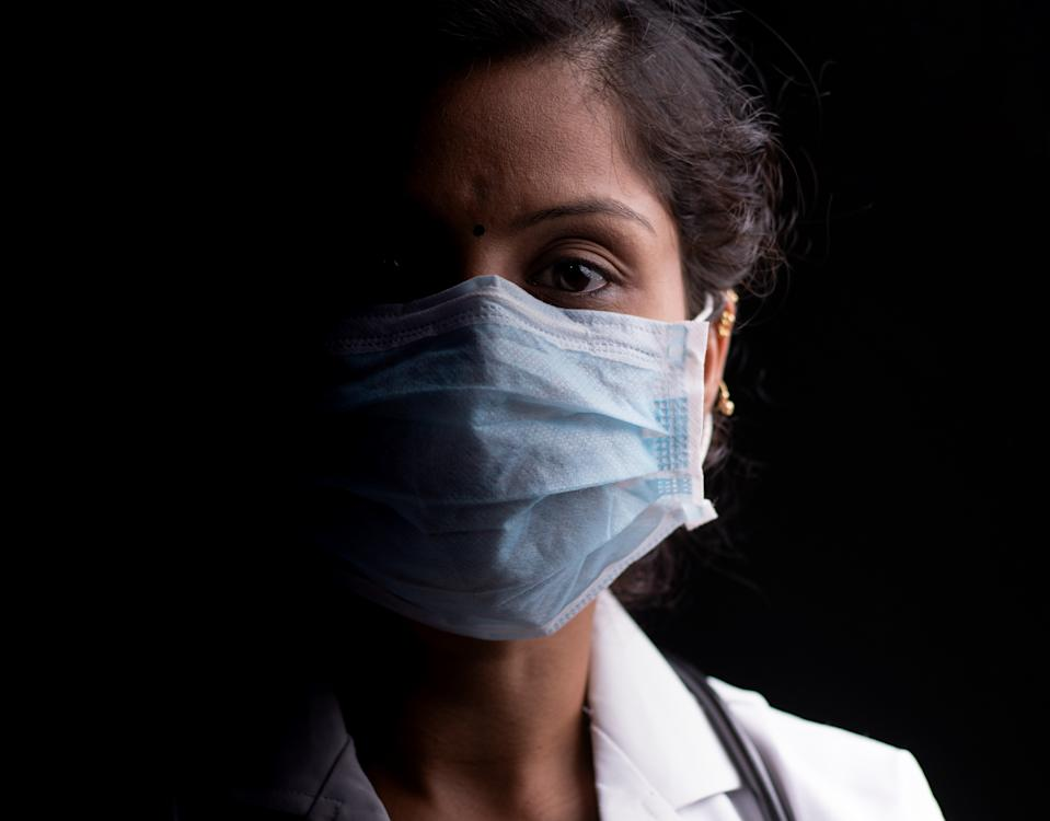 Close up of professional Medical doctor or nurse protective medical facial mask in dark room - Concept of covid-19 pandemic hope concept