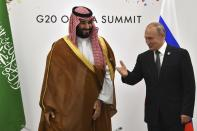 FILE - In this June 29, 2019, file photo, Russia's President Vladimir Putin, right gestures toward Saudi Arabia's Crown Prince Mohammed bin Salman during a meeting on the sidelines of the G20 Summit, in Osaka, Japan. The Nov. 21-22, 2020, Group of 20 summit, hosted by Saudi Arabia, will be held online this year because of the coronavirus. The gathering of leaders of the world's preeminent rich and developing nations will not be an opportunity for kings, presidents and prime ministers to conduct the intimate diplomacy of closed-door meetings or pose for memorable photo-ops. (Yuri Kadobnov/Pool Photo via AP, File)