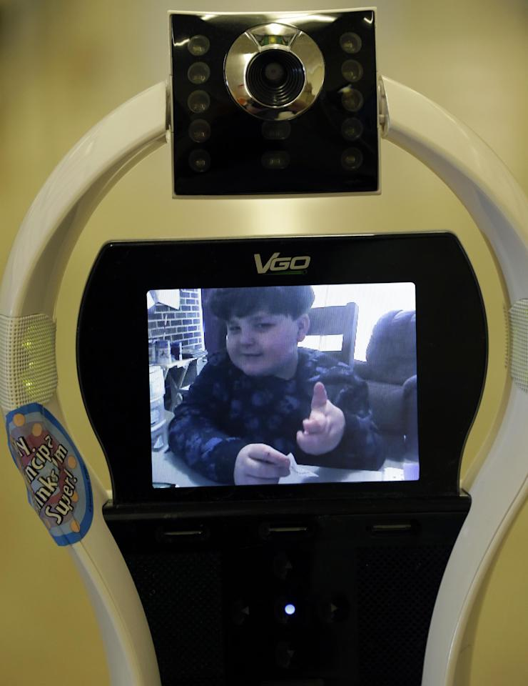In this Thursday, Jan. 24, 2013 photo, Devon Carrow attends Winchester Elementary School from home while operating a robot in the school, in West Seneca N.Y. Carrow's life-threatening allergies don't allow him to go to school. But the 4-foot-tall robot with a wireless video hookup gives him the school experience remotely, allowing him to participate in class, stroll through the hallways, hang out at recess and even take to the auditorium stage when there's a show. (AP Photo/David Duprey)