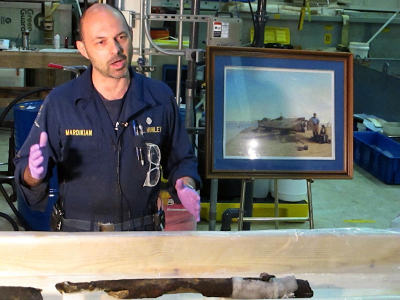 Conservator Paul Mardikian shows the remnants of a torpedo casing from the spar that was at the front of the Confederate submarine H.L. Hunley during a news conference in North Charleston, S.C., on Monday, Jan. 28, 2013. The discovery indicates the sub was no more than 20 feet from the Union blockade ship Housatonic when the Hunley sank it off South Carolina in 1864, becoming the first sub in history to sink an enemy warship. (AP Photo/Bruce Smith).