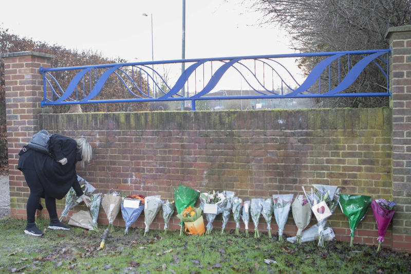 A woman lays flowers at the entrance to Debden Park High School, in Loughton, Essex, as a murder investigation has been launched after a 12-year-old boy was killed when a car crashed into children.