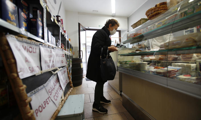 In this photo taken on Thursday, March 12, 2020, a woman buys food in a deli meat and cold cuts shop in Codogno, Italy. The northern Italian town that recorded Italy's first coronavirus infection has offered a virtuous example to fellow Italians, now facing an unprecedented nationwide lockdown, that by staying home, trends can reverse. Infections of the new virus have not stopped in Codogno, which still has registered the most of any of the 10 Lombardy towns Italy's original red zone, but they have slowed. For most people, the new coronavirus causes only mild or moderate symptoms. For some it can cause more severe illness. (AP Photo/Antonio Calanni)
