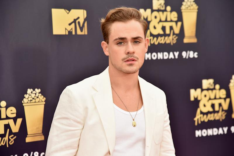 A photo of Dacre Montgomery wearing a white jacket on the red carpet at the MTV Movie & TV Awards in 2018.