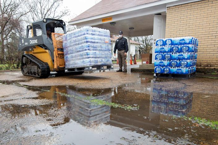 David Battaly, center, with MEMA, watches the delivery of pallets of bottled water at New Mount Zion Missionary Baptist Church on Maple Street shortly after noon Monday, March 1, 2021. MEMA, Mississippi Army National Guard and members of New Mount Zion Missionary Baptist Church manning the site, with publicized hours of operation beginning at 10 a.m., could offer hand sanitizer, face masks and non-potable water but no bottled water before the delivery. There were three pallets of water delivered for distribution.