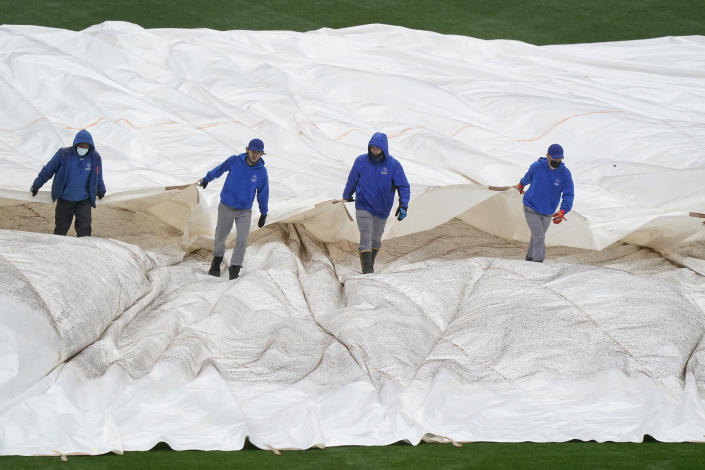 New York Mets groundskeepers pull a tarp over the outfield at Citi Field as a baseball game between the New York Mets and the Atlanta Braves was postponed due to rain, Sunday, May 30, 2021, in New York. (AP Photo/Kathy Willens)