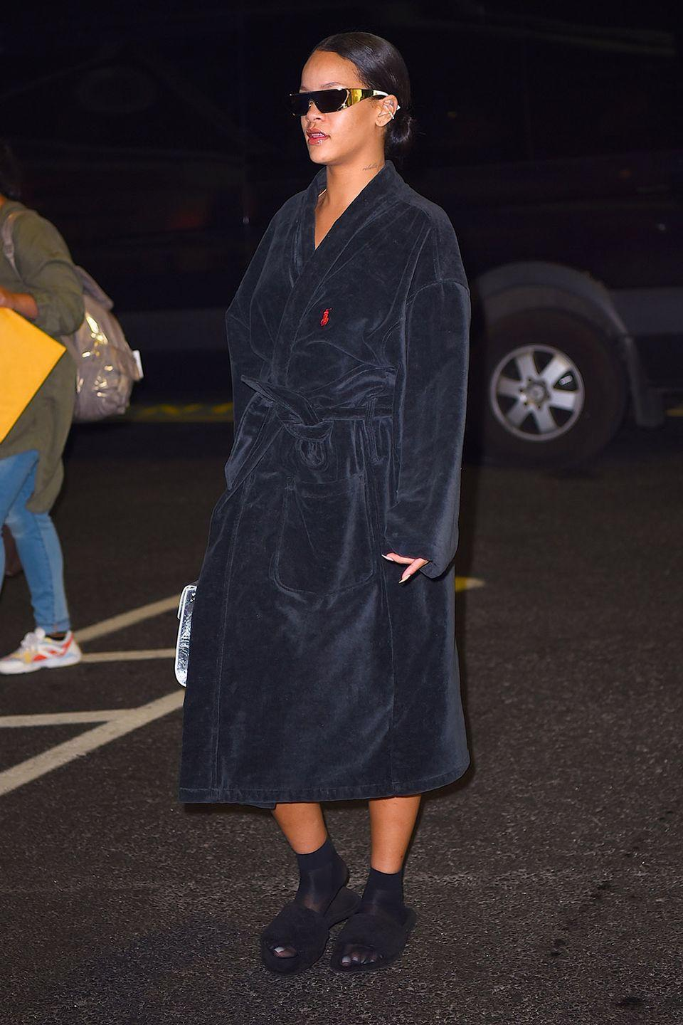 <p>Going casual in a navy robe, slippers, socks and her Dior collaboration sunglasses </p>