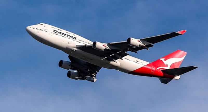 A Qantas plane takes off on a sunny day.