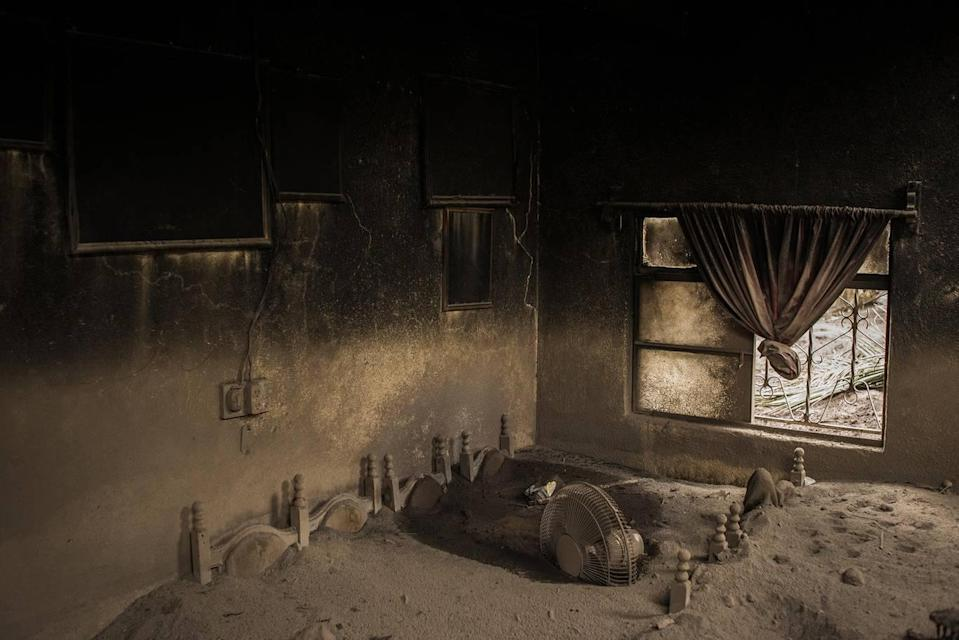 <p>The living-room of an abandoned home in San Miguel Los Lotes, Guatemala, lies covered in ash after the eruption of Volcán de Fuego on 3 June 2018. (Daniele Volpe) </p>