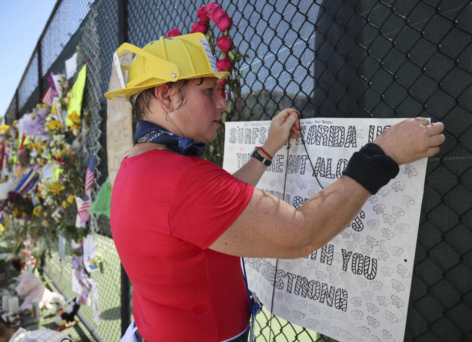 Hialeah resident Alison Kairuz, right, pins her hand-made sign to the fence in support of families and friends who lost love ones at the memorial site on Sunday, July 4, 2021 in Surfside, Fla. Demolition specialists carefully bored holes to insert explosive charges into the precarious, still-standing portion of a collapsed South Florida condo building that will come down to open up new areas for rescue teams to search. A top Miami-Dade fire official said 80% of the drilling work was complete and the remaining structure could come down as soon as Sunday night. (Carl Juste/Miami Herald via AP)