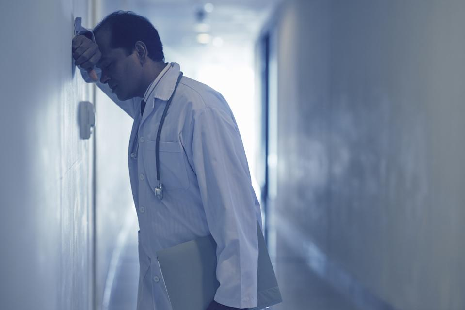 Upset male doctor standing at corridor and leaning against the wall