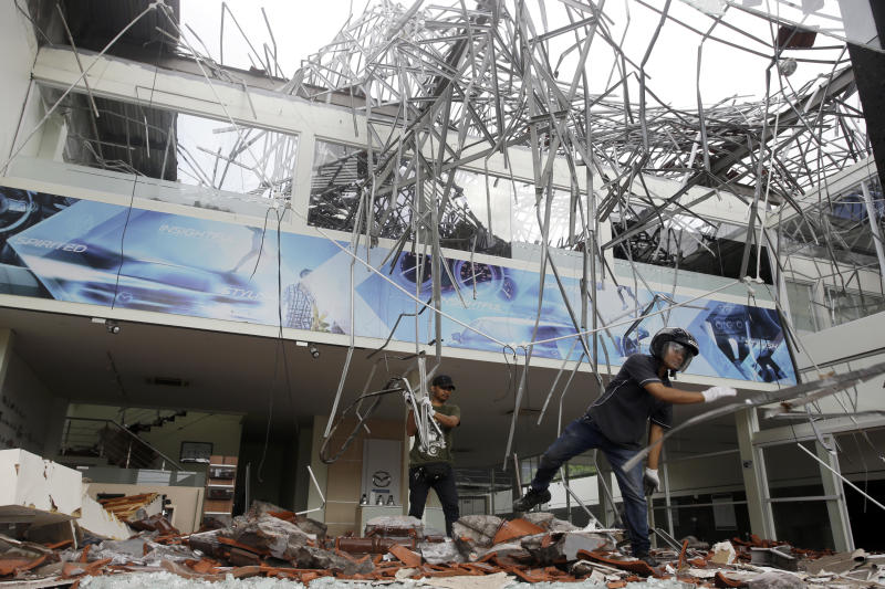 In this Monday, Aug. 6, 2018, file photo, workers remove the debris at a building damaged by an earthquake in Bali, Indonesia. A powerful earthquake struck the Indonesian tourist island of Lombok on Sunday, shaking neighboring Bali, one week after another quake on Lombok killed more than a dozen. (AP Photo/Firdia Lisnawati, File)