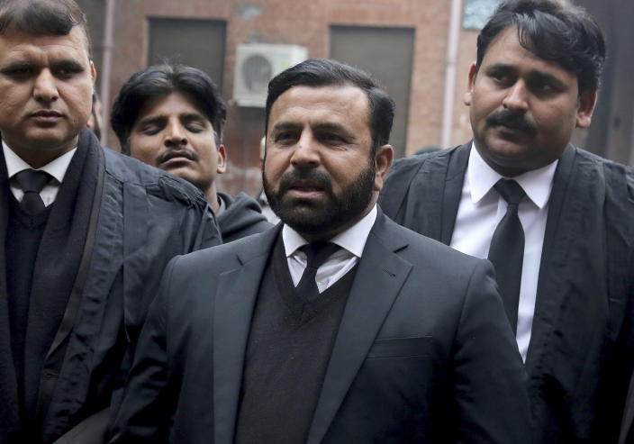 Ishtiaq Khan, a prosecutor, center, talks to journalists after a court decision, in Lahore, Pakistan, Monday, Jan. 13, 2020. The Pakistani court Monday overturned death sentence given to the country's ailing former dictator, saying a special court that last month convicted and sentenced Musharraf had been formed in violation of the law. (AP Photo/K.M. Chaudary)