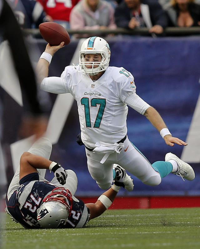 Miami Dolphins quarterback Ryan Tannehill passes the ball as he is tackled by New England Patriots defensive tackle Joe Vellano (72) in the second half of an NFL football game on Sunday, Oct. 27, 2013, in Foxborough, Mass. The Patriots won 27-17. (AP Photo/Michael Dwyer)