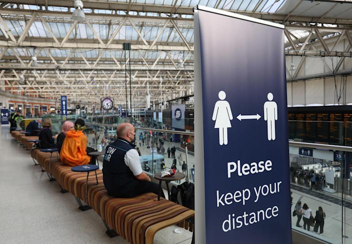 An information banner telling people to adhere to social distancing while sitting in London Waterloo train station as the bank holiday weekend approaches. Picture date: Friday August 28, 2020.