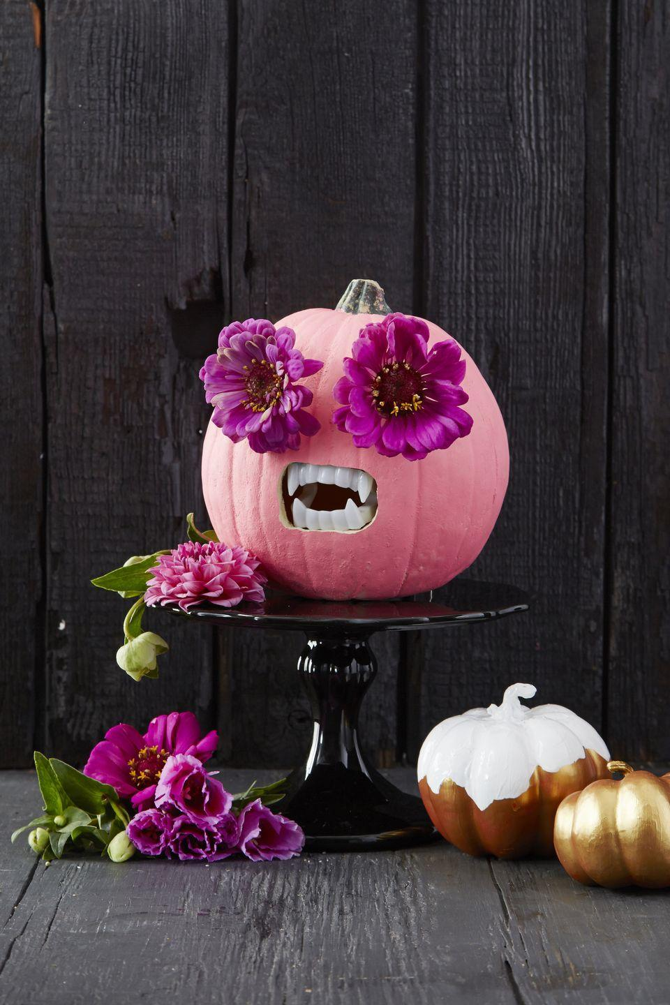 """<p>Use an awl to create eyeholes in a painted pumpkin, then push in the stems of two large blooms. To finish, carve a square for fake fangs.</p><p><a class=""""link rapid-noclick-resp"""" href=""""https://www.amazon.com/Vampire-Plastic-Costume-Accessory-Favors/dp/B003O6F9RQ?tag=syn-yahoo-20&ascsubtag=%5Bartid%7C10055.g.1566%5Bsrc%7Cyahoo-us"""" rel=""""nofollow noopener"""" target=""""_blank"""" data-ylk=""""slk:SHOP PLASTIC FANGS"""">SHOP PLASTIC FANGS</a></p>"""