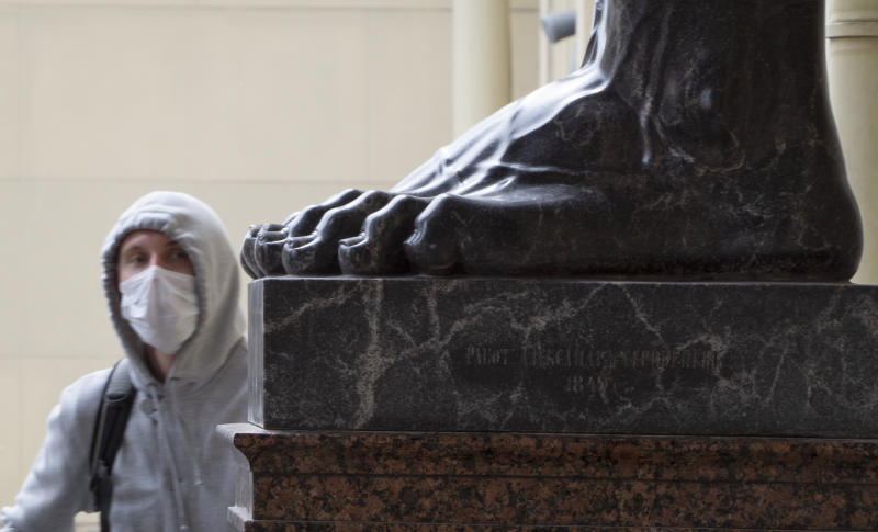 A man wearing a face mask to protect against coronavirus looks at the feet of a famous sculpture of Atlas at the State Hermitage museum amid the ongoing COVID-19 pandemic in St.Petersburg, Russia, Thursday, May 28, 2020. (AP Photo/Dmitri Lovetsky)