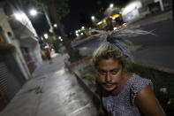 Sex worker Angora, 27, sits along the street as she tries to earn money after having her bag stolen by a man pretending to be a client, near the Revolution subway station in Mexico City, Thursday, March 25, 2021. Conditions that have always been tough for the women who ply the trade in Mexico City - violence by clients and gangs who prey on prostitutes, and shakedowns by corrupt police - have gotten even worse during the coronavirus pandemic. (AP Photo/Rebecca Blackwell)