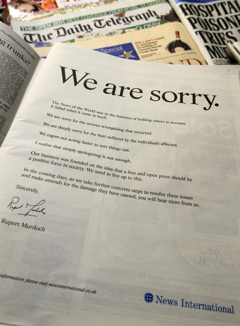 """A newspaper is opened to show the advertisement apology for News International and photographed at a news vendor in central London, Saturday, July 16, 2011.  News Corporation chairman Rupert Murdoch signed the company advert entitled """"We are sorry"""",  which is published in British national newspapers Saturday.  The News International publication News of the World is accused of hacking into the mobile phones of various crime victims, celebrities and politicians.  (AP Photo/Sang Tan)"""