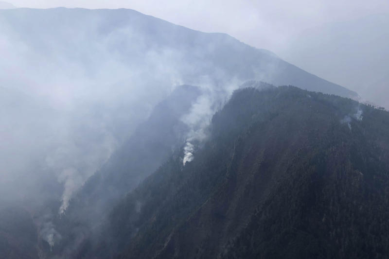 In this aerial photo released by Xinhua News Agency, smoke can be seen from a forest fire in Yalongjiang township of Muli County, Liangshan Yi Autonomous Prefecture in southwestern China's Sichuan Province on Monday, April 1, 2019. The fire high in the mountains of western China's Sichuan province has killed over two dozen firefighters and others, the government said Monday. (Lin Jiping/Xinhua via AP)