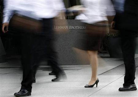 People walk past a sign of Lehman Brothers Holdings in front of the company's branch in Tokyo September 16, 2008