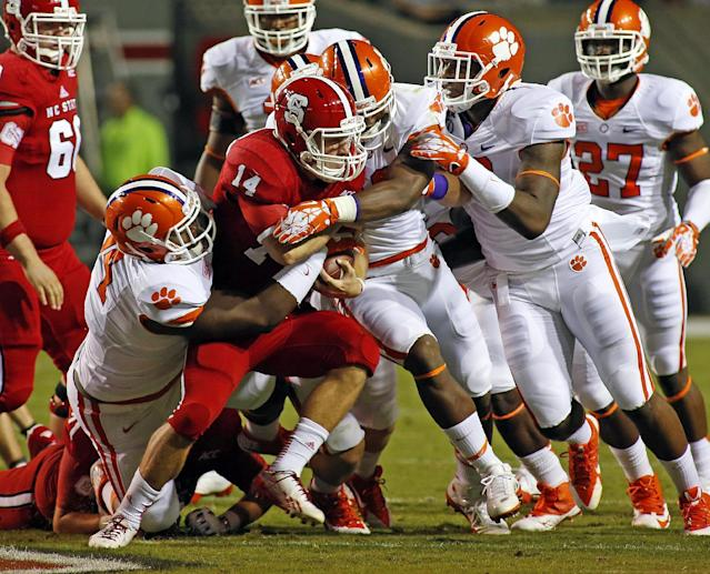 Clemson's Carlos Watkins, left, Stephone Anthony, center, and Corey Crawford tie up North Carolina State's Bryant Shirreffs (14) with Clemson's Robert Smith (27) nearby during the first half of an NCAA college football game in Raleigh, N.C., Thursday, Sept. 19, 2013. Clemson won 26-14. (AP Photo/Karl B DeBlaker)