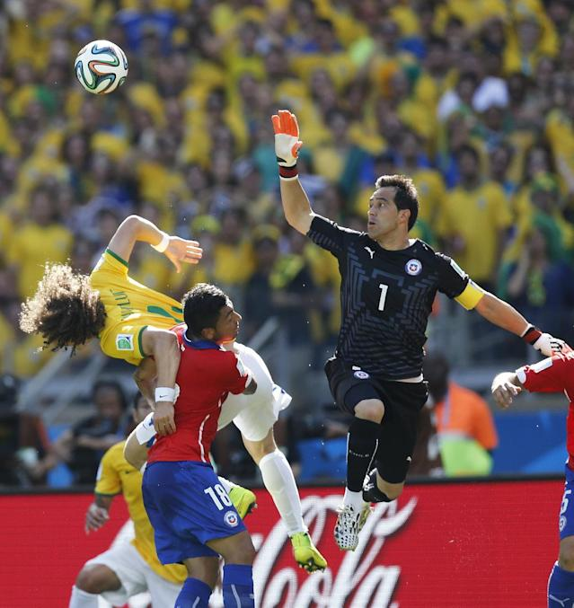 Chile's goalkeeper Claudio Bravo jumps for the ball as Brazil's David Luiz and Chile's Gonzalo Jara go for a header during the World Cup round of 16 soccer match between Brazil and Chile at the Mineirao Stadium in Belo Horizonte, Brazil, Saturday, June 28, 2014. (AP Photo/Frank Augstein)
