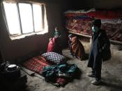 Internally displaced Afghan family sit at their shelter on the outskirts of Kabul