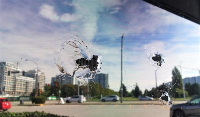 Bullet holes are seen in the window of the Manzo Itamae Japanese Restaurant in Richmond, BC, where accused money launderer Jian Jun Zhu was shot dead last week. Photo: Ian Young