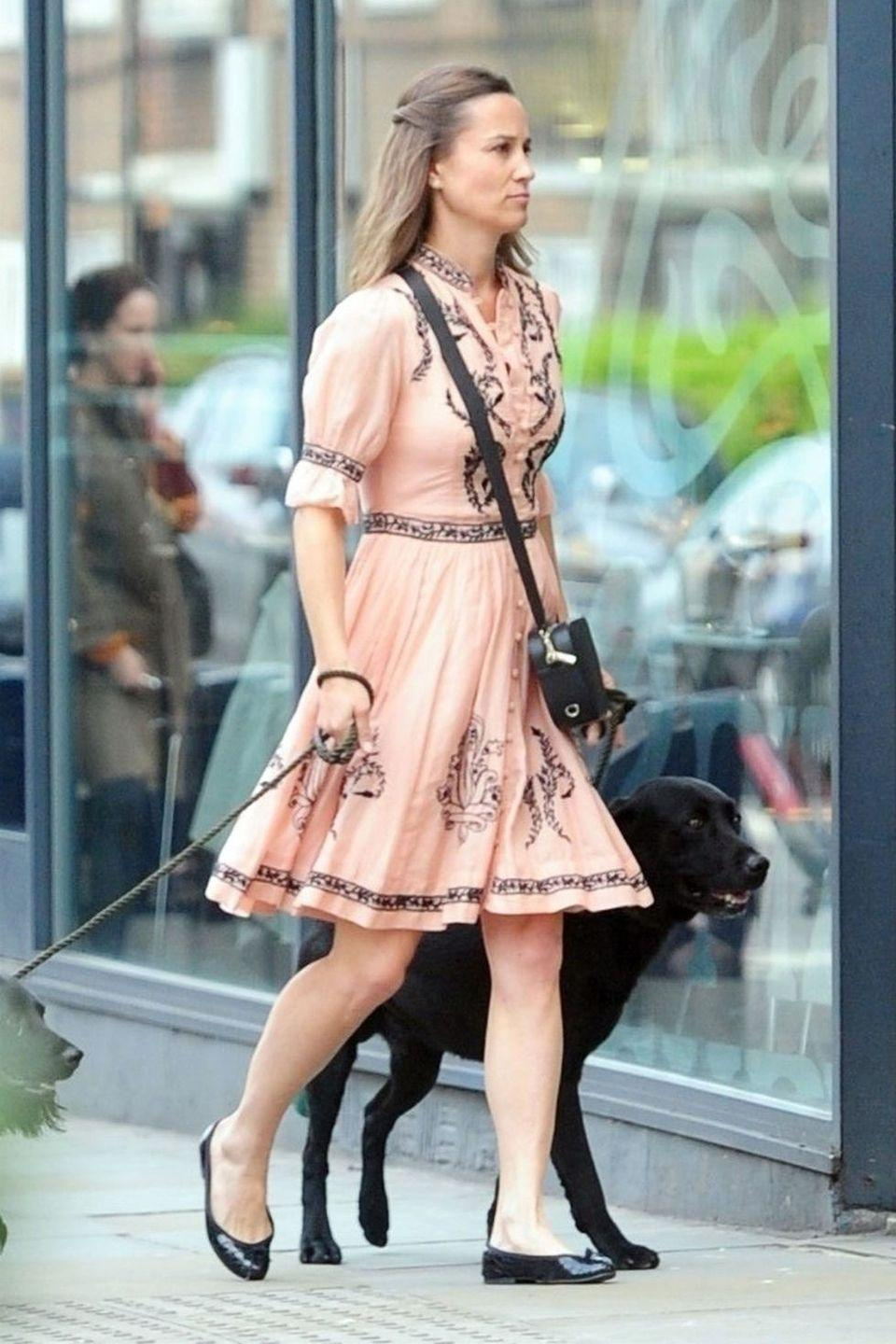<p>In a coral embroidered dress and black ballet flats. </p>