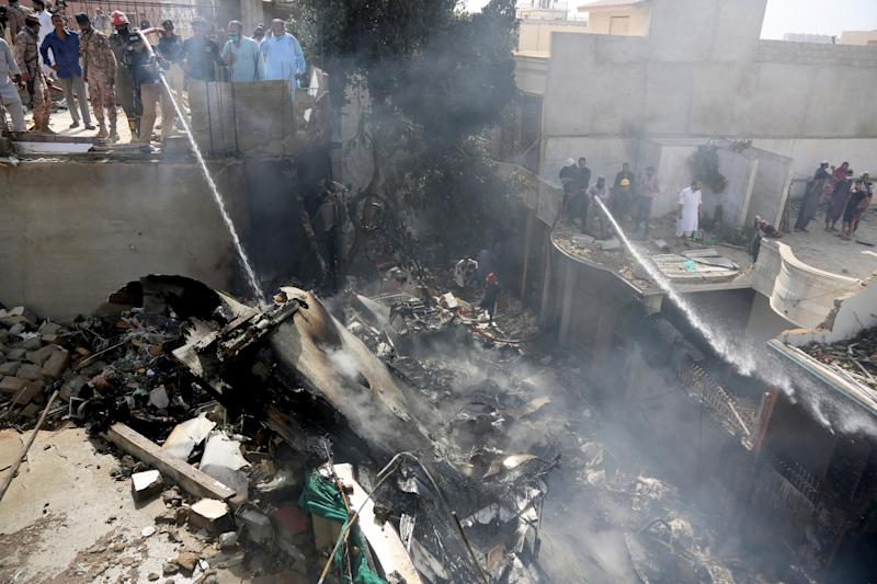 Fire brigade staff try to put out fire caused by plane crash in Karachi, Pakistan, Friday, May 22, 2020. An aviation official says a passenger plane belonging to state-run Pakistan International Airlines carrying more than 100 passengers and crew has crashed near the southern port city of Karachi. There were no immediate reports on the number of casualties. (AP Photo/Fareed Khan