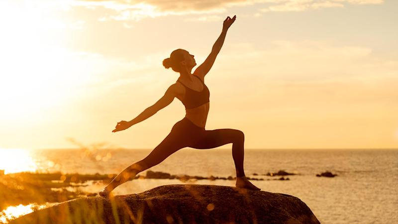 caucasian fitness woman practicing yoga at sunset.