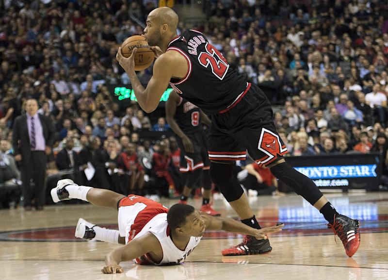 Toronto Raptors guard Kyle Lowry, bottom left, falls as Chicago Bulls forward Taj Gibson, right, moves the ball during second-half NBA basketball game action in Toronto, Friday, Nov. 15, 2013. (AP Photo/The Canadian Press, Nathan Denette)
