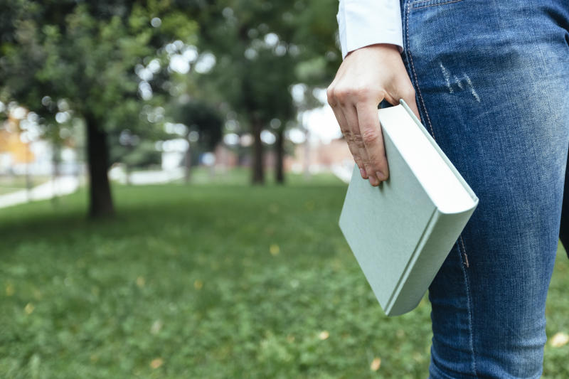 Girl walking in park, carrying book, close up