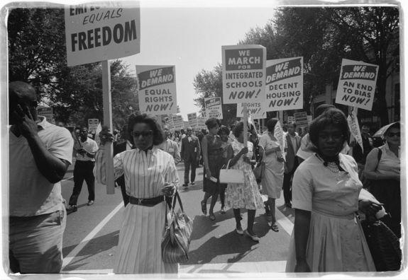African-Americans carrying signs for equal rights, integrated schools, decent housing and an end to bias during the 1963 March on Washington.