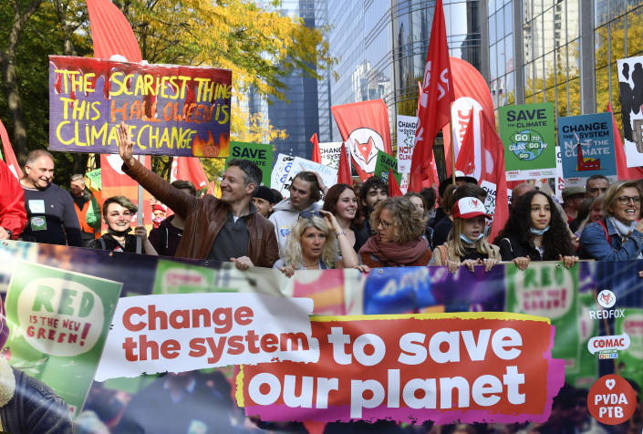 Protestors hold banners and signs as they participate in a climate march in Brussels, Sunday, Oct. 10, 2021. Some 80 organizations are joining in a climate march through Brussels to demand change and push politicians to effective action in Glasgow later this month.(AP Photo/Geert Vanden Wijngaert)