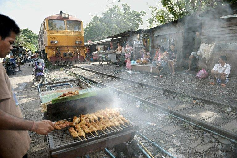 A man cooks barbecue chicken as a train passes by shack houses in Bangkok on October 28, 2008
