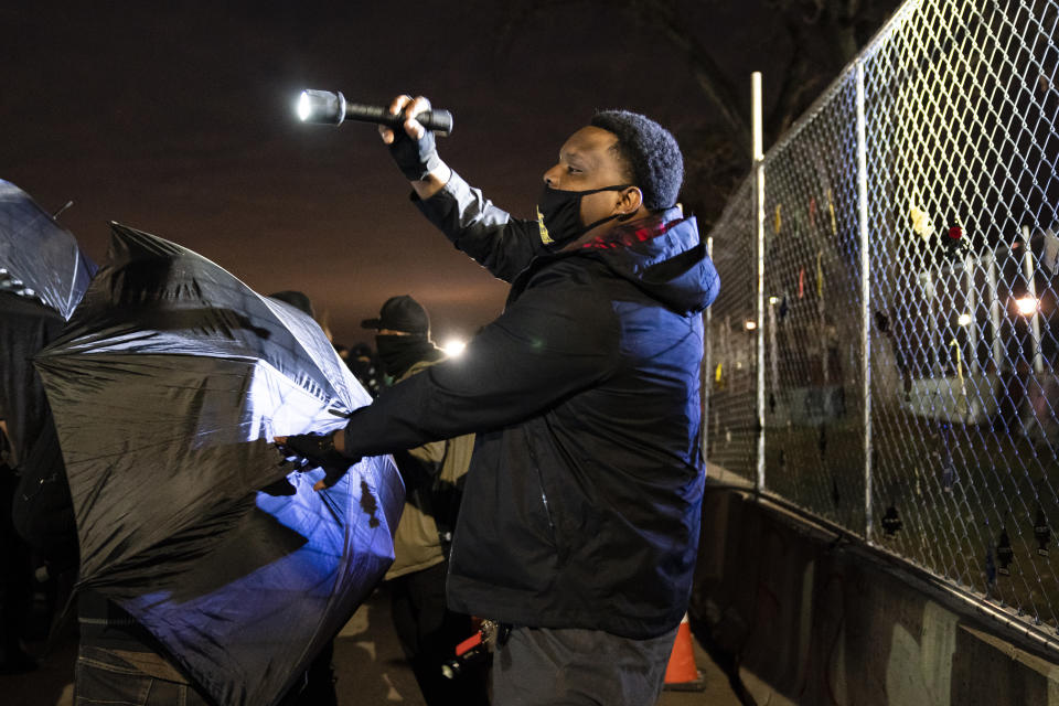 Black men attempt to deescalate demonstrators using umbrellas to press against a perimeter fence and agitate authorities during a protest decrying the shooting death of Daunte Wright outside the Brooklyn Center Police Department, Thursday, April 15, 2021, in Brooklyn Center, Minn. (AP Photo/John Minchillo)