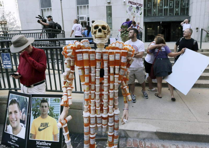FILE - In this Friday, Aug. 2, 2019 file photo, a skeleton made of pill bottles stands with protesters outside a courthouse in Boston, where a judge was to hear arguments in Massachusetts' lawsuit against Purdue Pharma over its role in the national drug epidemic. The skeleton was created by Frank Huntley, of Worcester, Mass., from prescriptions he said he received while addicted to opioids. Organizers of the protest said they wanted to continue to put pressure on the Connecticut pharmaceutical company and the Sackler family that owns it. (AP Photo/Charles Krupa)