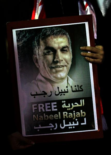 """A Bahraini anti-government protester holds the image of jailed human rights activist Nabeel Rajab, during a rally outside Rajab's home in Bani Jamra, Bahrain, Monday, Dec. 10, 2012. A court session is scheduled for Tuesday in Rajab's appeal of a three-year sentence handed down for calling for and participating in unauthorized demonstrations. Arabic on the poster reads, """" we are all for Nabeel Rajab, Free Nabeel Rajab."""" (AP Photo/Hasan Jamali)"""