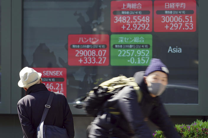 A man looks at an electronic stock board showing Japan's Nikkei 225 and the Asian indexes at a securities firm in Tokyo Friday, April 9, 2021. Shares fell Friday in most Asian markets after China reported a stronger than expected rise in prices that could prompt authorities to act to cool inflation. (AP Photo/Eugene Hoshiko)