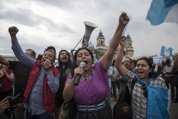 People protest against a decision by Guatemala's President Jimmy Morales to shut down the United Nations International Commission Against Impunity, CICIG, at Constitution Square in Guatemala City, Friday, Aug. 31, 2018. Last week the Supreme Court allowed a request brought by the CICIG and Guatemalan prosecutors to strip Morales' immunity from prosecution to go to Congress for consideration. (AP Photo/Oliver de Ros)