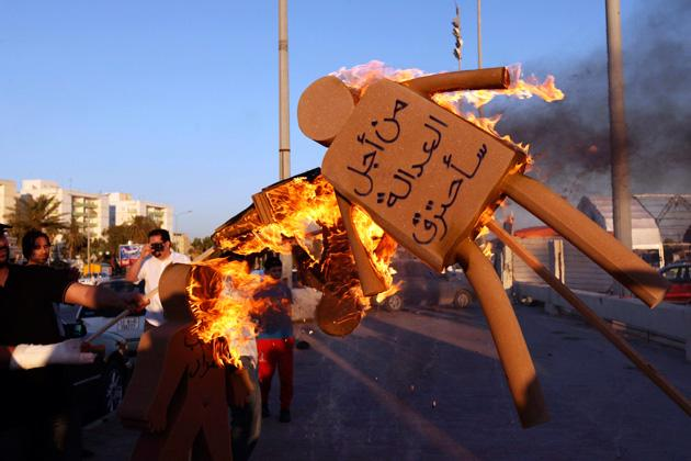 "Men set fire to sponge dolls, representing the demonstrators' rejection of the current allocation of seats in the elections for Libya's National Congress, during a protest in Benghazi June 9, 2012. The words on the doll on the right read: ""For justice will be burned"".   REUTERS/Esam Al-Fetori"