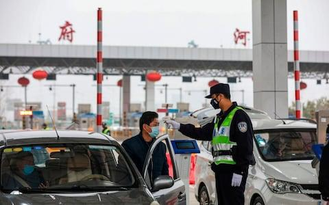 A police officer checks the temperature of a driver at a highway in Wuhan, China - Credit: Getty Images