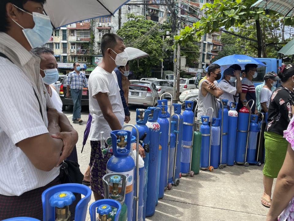 People queue up with their oxygen tanks outside an oxygen refill station in Pazundaung township in Yangon, Myanmar, Sunday, July 11, 2021. Myanmar is facing a rapid rise in COVID-19 patients and a shortage of oxygen supplies just as the country is consumed by a bitter and violent political struggle since the military seized power in February. (AP Photo)