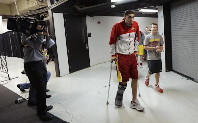 Iowa State's Georges Niang, center, arrives in uniform for practice for the NCAA men's college basketball tournament, Saturday, March 22, 2014, in San Antonio. Niang broke his foot during a game Friday night and will not play when Iowa State faces North Carolina on Sunday. (AP Photo/Eric Gay)