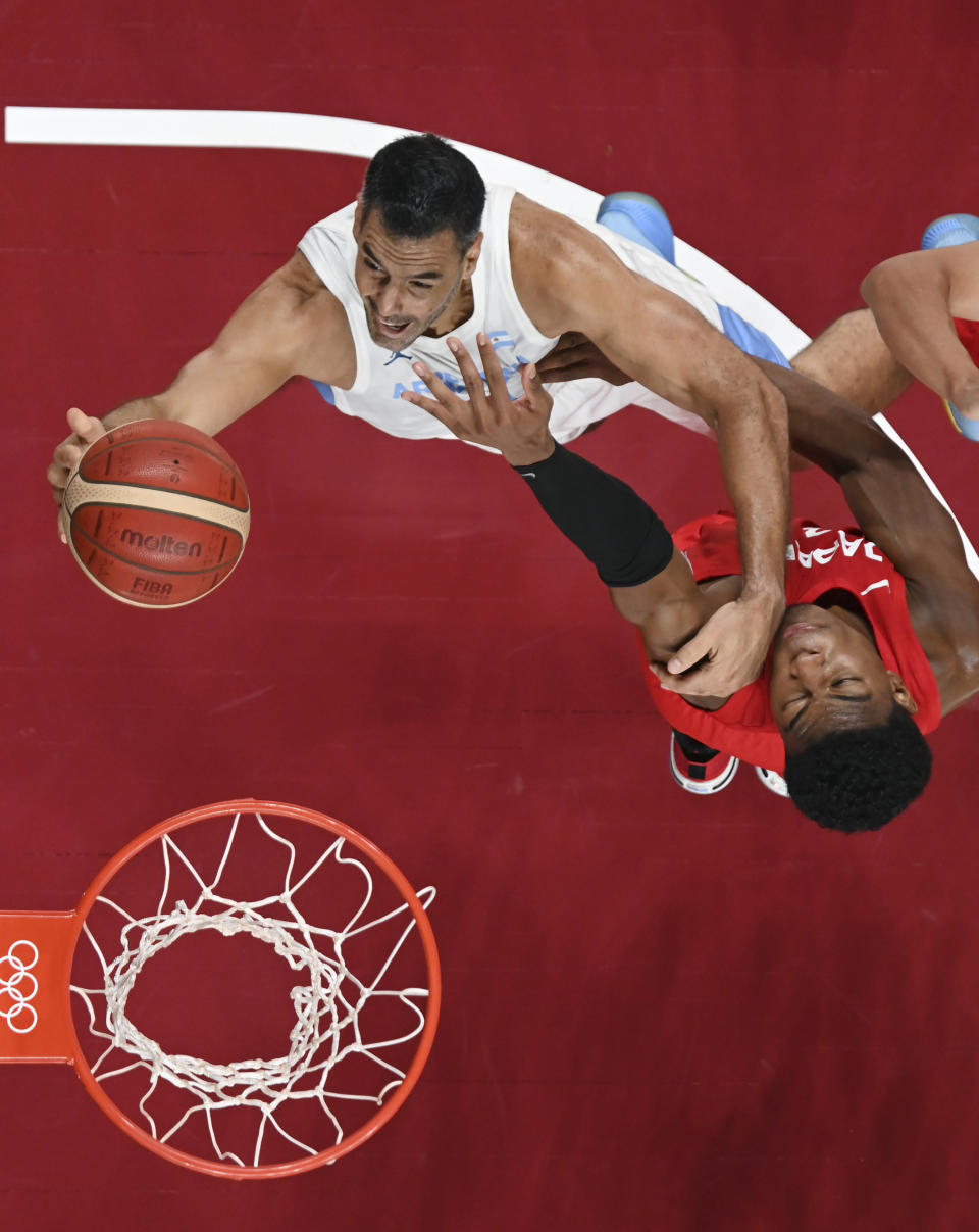 Argentina's Luis Scola, left, drives to the basket against Japan's Rui Hachimura, right, during a men's basketball game at the 2020 Summer Olympics, Wednesday, July 28, 2021, in Saitama, Japan. (Aris Messinis/Pool Photo via AP)