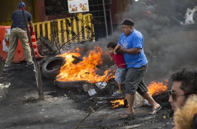 <p>A man carries a boy as they cross a burning barricade erected by supporters of presidential candidate Salvador Nasralla protesting the officials results that have trickled out giving incumbent President Juan Orlando Hernandez a growing lead, in Tegucigalpa, Honduras, Friday, Dec. 1, 2017. (Photo: Rodrigo Abd/AP) </p>
